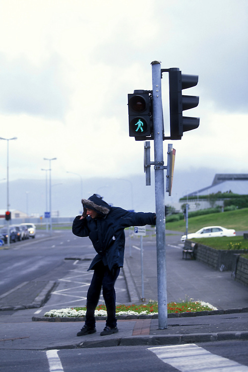 Europe, Iceland, Reykjavik, Pedestrian struggles through 40 mph summer wind storm in city's downtown