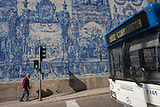 An elderly gentleman walks uphill on the Rua de Fernandes Tomas where a bus has stopped at lights and Azulejo tiles are seen on the exterior of Capela Das Almas, on 19th July, in Porto, Portugal. The Church's magnificent panels depict scenes from the lives of various saints, including the death of St Francis and the martyrdom of St Catherine. Eduardo Leite painted the tiles in a classic 18th-century style, though they actually date back only to the early 20th century. (Photo by Richard Baker / In Pictures via Getty Images)