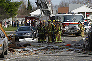 Firefighters and onlookers near houses in the 300 block of Wayne Drive damaged or destroyed by what appears to be a gas-line explosion in Fairborn, Saturday, November 12, 2011.