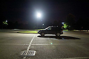 single car in parking lot at night