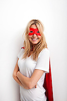 Portrait of confident woman in superhero costume against white background