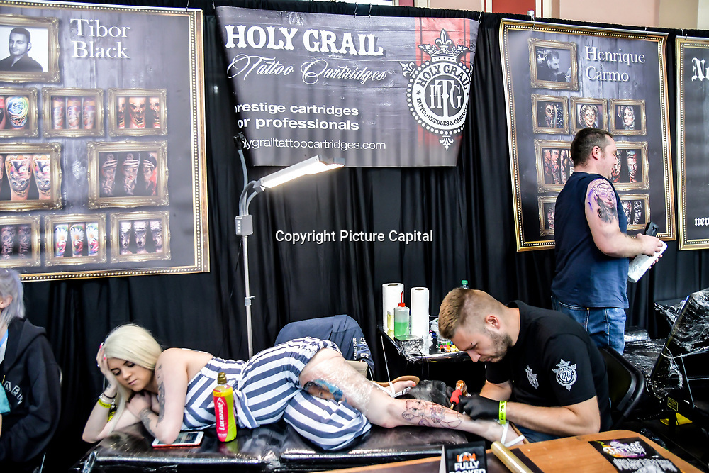 Holy Grail tattoo cartridges, Tattoo a client at The Great British Tattoo Show, on 26 May 2019, London, UK.