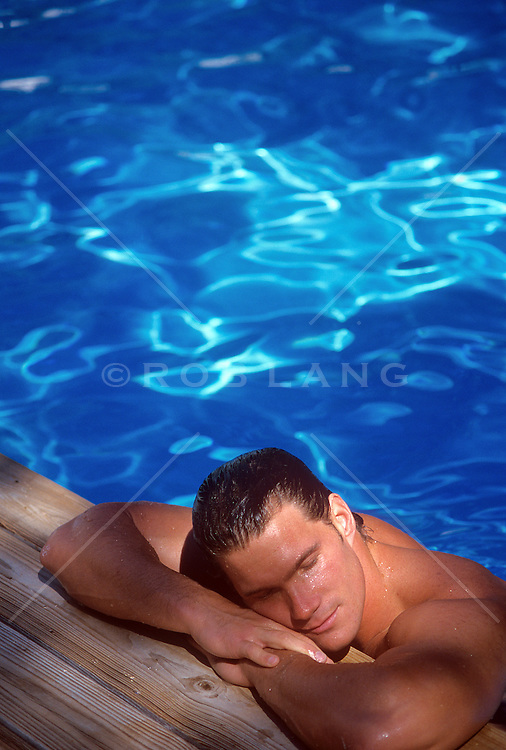 man enjoying time in a swimming pool at the edge of the pool