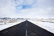 The main tarmac road route to and from Reykjavik though lava fields in South Iceland with snow depth markers on the roadside.