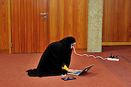 Iran state TV anchor woman wearing Islamic dress with computer mobile phone and tablet at the press center during the first round of the E3/EU+3 Iran talks in Geneva concerning Iran's nuclear program. E3/EU +3 refers to UK, France and Germany plus U.S., Russia and China.