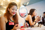 A contestants for the Miss Universe China Pageant  practices her smile in the mirror at a training camp for contestants in Beijing, China on Thursday, June 23, 2011.   The training camp was created by cosmetics businesswoman and Chinese-American television personality Yue-Sai Kan's to give China, which has never won a Ms. Universe Contest, a cpotential contender in the upcoming beauty pagent.