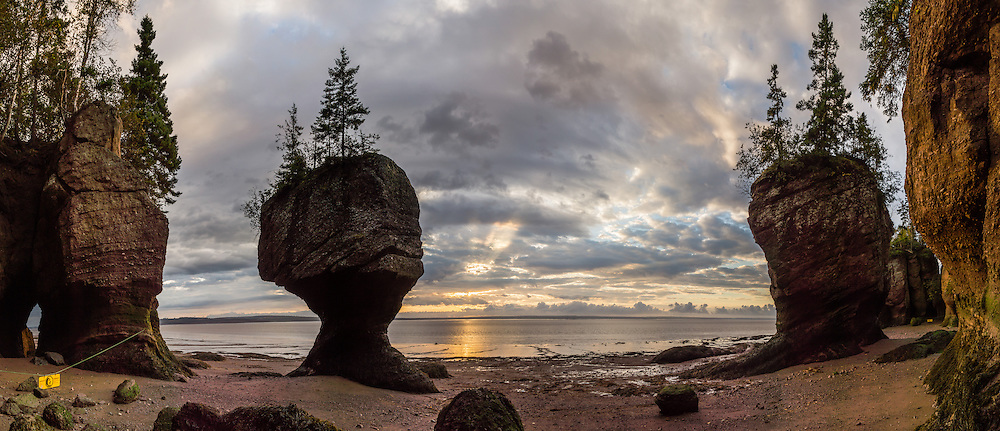 Sunrise. Visit Hopewell Rocks (Flowerpot Rocks) at Hopewell Cape, near Moncton, New Brunswick, Canada. Hopewell Rocks have one of most extreme tidal ranges in the world: up to 16 meters (52 feet) vertically. Waves and tides twice per day have eroded the base of the rocks faster than the tops, leaving arches and curiously shaped formations of dark sedimentary conglomerate and sandstone rock. For best photo lighting, go in morning (or spectacular sunrise) during the first low tide of the day, safe for 3 hours before low tide until 3 hours after. Walking the beach is easy until its southern end, where The Ledges, a ridge of slippery limestone, can be clambered over to reach Demoiselle Beach. Bay of Fundy has the highest tidal range in the world, due to a resonance of being just the right length (270 km) matching the gravitational pushing cycle of the Moon that causes the tides. Due to the bay's optimal size, the time it takes a large wave to go from the mouth of the bay to the inner shore and back is practically the same as the time from one high tide to the next. (See the effect of resonance by steadily pushing a long pan of water back and forth: an optimal pushing frequency for a given pan size will build up a high wave of water which sloshes out; but pushing too fast or too slow won't build up the big wave.) Two high tides occur per day, one when the ocean side of the Earth is nearest the Moon, and one on the side most distant from the Moon, about 12 hours and 25 minutes from one high tide to the next. The Bay of Fundy is on the Atlantic coast of North America, on the northeast end of the Gulf of Maine between the Canadian provinces of New Brunswick and Nova Scotia. Address: Hopewell Rocks Ocean Tidal Exploration Site (phone 506-734-3429), 131 Discovery Rd, Hopewell Cape, NB E4H 4Z5. The panorama was stitched from 12 overlapping photos.
