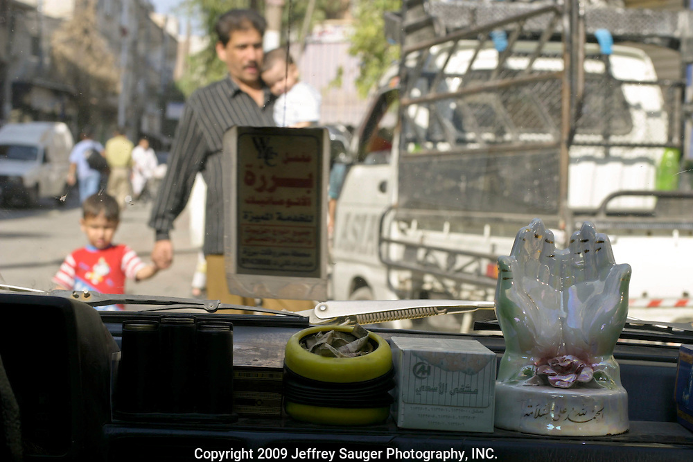 """Thank God for being safe,"" reads the inscription on the bottom of the hands icon as a man and his children get out of the way of a taxi driver weaving between traffic in Damascus, Syria, Friday, July 18, 2003."