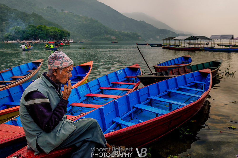 an old man smoking on a colorful canoe of Pokhara lake, Nepal