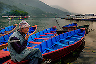 an old man smoking on a colorful canoe of Pokhara lake, Nepal