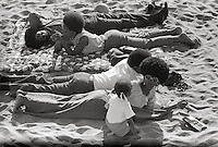 Couples with children resting at on the beach in California 1960's