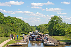 """© Licensed to London News Pictures. 22/06/2019. Hatton, Warwickshire, UK. Narrowboats ascend the Hatton Flight, or """"stairway to heaven"""", a flight of 21 locks on the Grand Union Canal during a hot summers day Warwickshire. Photo credit: LNP"""