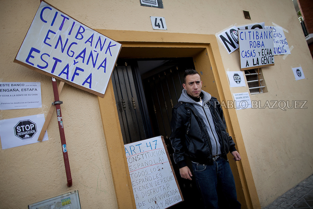Vicente's Grandson, Jonathan Torres 24 stands at the entrance with anti-eviction banners outside Vicente's building , on April 18 2012, in Madrid, Spain. Spanish Vicente Torres, 73, who is severely ill and underwent a recent heart surgery, and is waiting for a thrombus surgery faces an eviction from his house after he endorsed his son, so Citibank would concede a credit to buy a house. His son already handed his house to the bank. Torres has lived at his home for the last 55 years and was paying it for 30 years. Eviction procedures in Spanish courts for unpaid mortgages and rent hit a record of 58,241 in 2011, a 21.2 percent rise over the previous year. Evictions have soared in Spain since the collapse of a property bubble in 2008 that triggered the country's economic crisis.