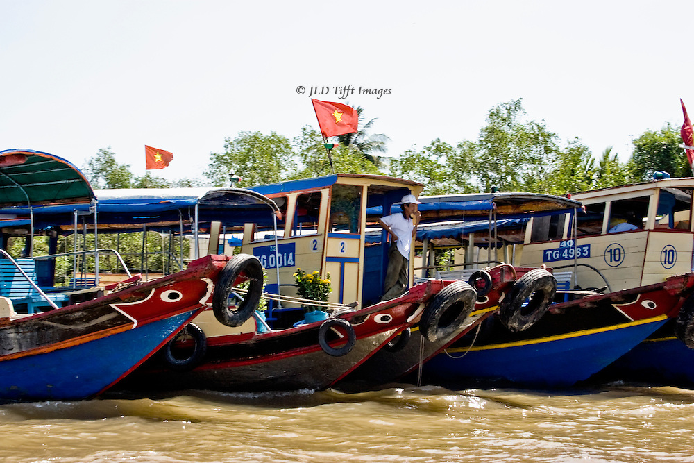 Tourist boats moored on the shore of the Mekong, in the delta.  Decorative motives on the bows, covered passenger area, Vietnamese flags flying.  One boatman stands on the bow of the middle vessel as though waiting for someone.