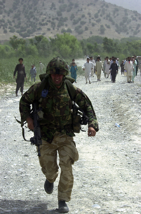 "A British Royal Marines 45 Commando runs to board a Chinook helicopter during an ""eagle vehicle check point"" (VCP) mission as part of the ongoing Operation Buzzard July 8, 2002 in southeastern Afghanistan. During VCPs, small groups of marines are dropped quickly by helicopters to search random vehicles on dirt roads and trails near the Pakistan-Afghanistan border to deny al Qaeda and Taliban fighters freedom of movement across the region."