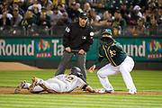 San Francisco Giants second baseman Joe Panik (12) dives to first base as Oakland Athletics first baseman Yonder Alonso (17) makes a catch at Oakland Coliseum in Oakland, California, on July 31, 2017. (Stan Olszewski/Special to S.F. Examiner)
