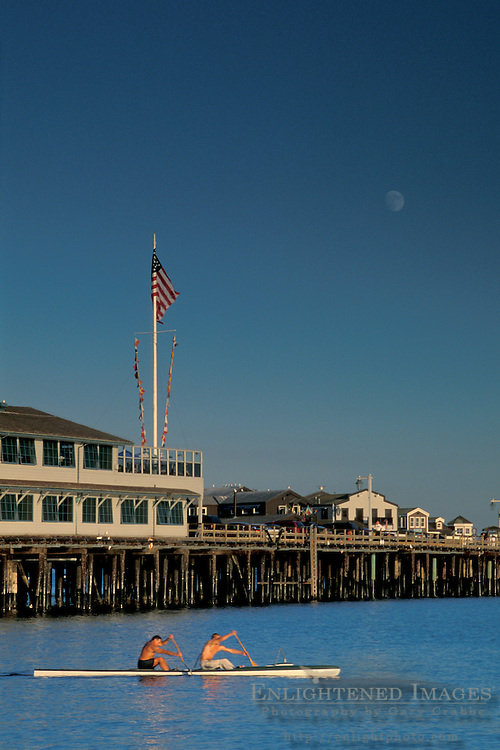 Moon rising over two men paddle shell boat in front of Stearns Wharf, Santa Barbara, Southern Coast, California