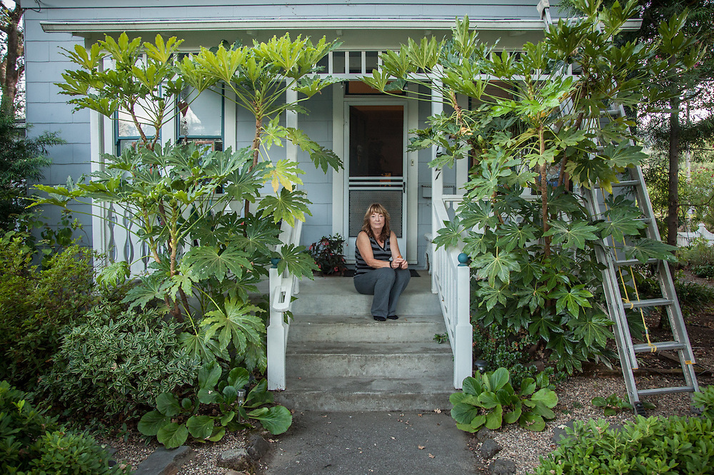 """Nanci M. Smith on her porch of her home on Cedar Street in Calistoga.  """"A branch from one of my 300 year old trees fell in July and took out the corner of my porch...I went into the house for a drink of water and it saved my life."""""""