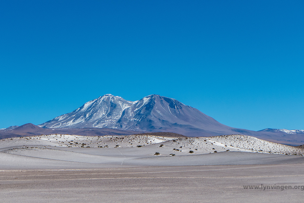 Andean landscape, Atacama desert north Chile. Volcanic ash in the foreground and snow on the peaks in the background