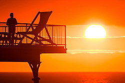 © Licensed to London News Pictures. 23/07/2018. Aberystwyth, UK. People silhouetted by the glorious setting sun over Aberystwyth pier at the end of the hottest day of the summer so far, with temperatures peaking at 33.3∫c in Santon Downham, Suffolk .  The UK wide heatwave continues, with no respite from the very dry weather , and the Met Office has issued a 'heat health watch alert'  for much of the east and south-east of England. Photo credit: Keith Morris/LNP