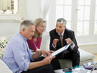 Senior couple sitting on sofa with financial advisor elevated view