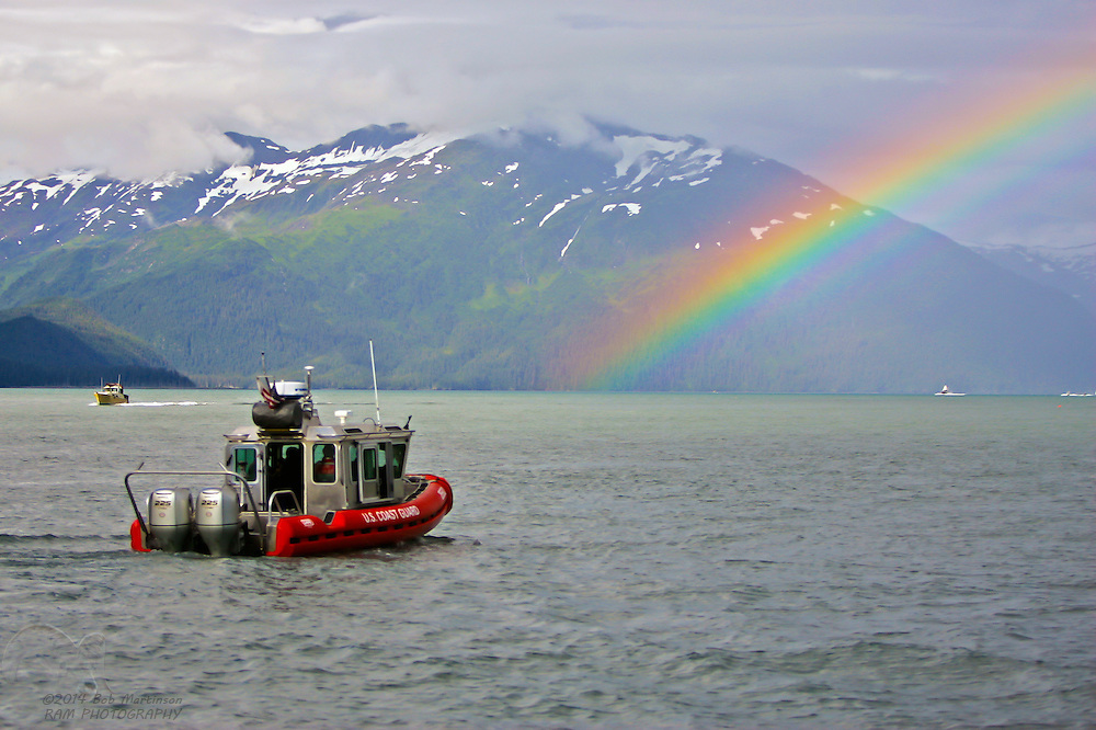 A United States Coast Guard vessel patrols Alaska's Prince William Sound as it travels toward a brilliant rainbow.