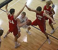 Cedar Rapids Xavier's Adam McDermott (3) eyes the basket between the arms of Ottumwa's Aaron Roane (34) and Cater Burns (40) during their game at Xavier High School in Cedar Rapids on December 10, 2013.