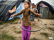 "05 AUGUST 2015 - KATHMANDU, NEPAL: A girl plays with a home made ""Hula Hoop"" type toy in a large Internal Displaced Person (IDP) Camp in the center of Kathmandu. The camp is next to one the most expensive international hotels in Kathmandu. More than 7,100 people displaced by the Nepal earthquake in April live in 1,800 tents spread across the space of three football fields. There is no electricity in the camp. International NGOs provide water and dug latrines on the edge of the camp but the domestic waste water, from people doing laundry or dishes, runs between the tents. Most of the ground in the camp is muddy from the running water and frequent rain. Most of the camp's residents come from the mountains in northern Nepal, 8 - 12 hours from Kathmandu. The residents don't get rations or food assistance so every day many of them walk the streets of Kathmandu looking for day work.    PHOTO BY JACK KURTZ"