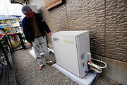 Kunihiro Tonegawa stands by the hydrogen power generator installed outside ahis home in Maebaru - otherwise known as Hydrogen Town - in Fukuoka, Japan.