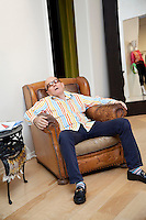 Tired senior man sitting on armchair in fashion boutique