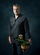 Studio Portrait of Josef, florist and owner of Floral Botanical Design holding an orchid