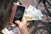 photographing raw herring with the traditional Dutch flag pickles and unions in Amsterdam