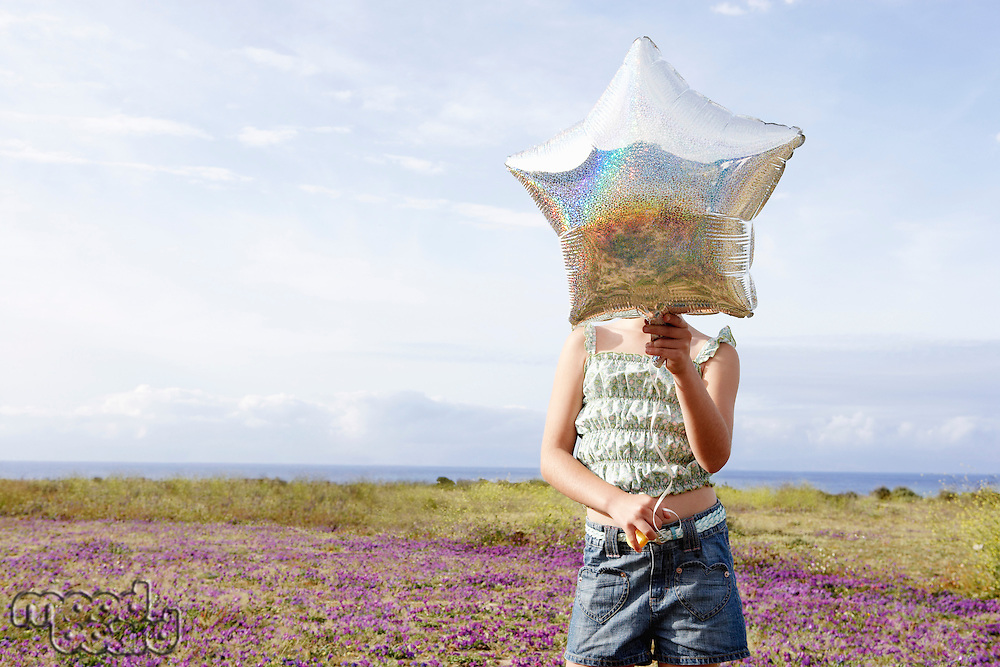 Little Girl Holding a Balloon in front of face in field of flowers