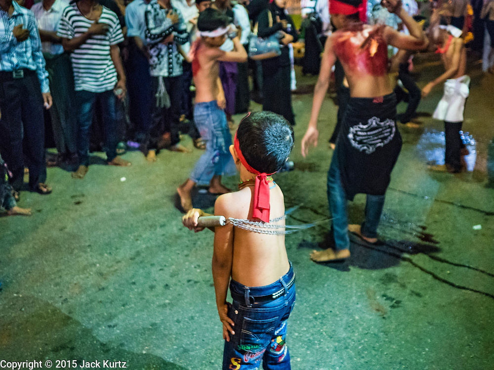 23 OCTOBER 2015 - YANGON, MYANMAR:  Shia boys and teenagers participate in ritual self flagellation with razors and chains during Ashura observances at Mogul Mosque in Yangon. Ashura commemorates the death of Hussein ibn Ali, the grandson of the Prophet Muhammed, in the 7th century. Hussein ibn Ali is considered by Shia Muslims to be the third imam and the rightful successor of Muhammed. He was killed at the Battle of Karbala in 610 CE on the 10th day of Muharram, the first month of the Islamic calendar. According to Myanmar government statistics, only about 4% of the population is Muslim. Many Muslims have fled Myanmar in recent years because of violence directed against Burmese Muslims by Buddhist nationalists.    PHOTO BY JACK KURTZ