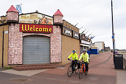 Portobello, Scotland, UK. 28 March, 2020. On the first weekend of the coronavirus lockdown the public were outdoors exercising and maintaining social distancing along Portobello beachfront promenade. Pictured; cyclists on promenade and closed amusement arcade. Iain Masterton/Alamy Live News