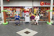 Nederland, EIndhoven, 20160701.<br /> Voor het Kruidvat in Winkelcentrum Woensel <br /> Zittend op een bankje in het overdekte winkelcentrum.<br /> Aan weerszijden een plastic opblaasbare palmboom ter decoratie.