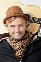Portrait of happy young Caucasian man with guitar over white background