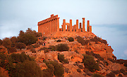 Low angle view of the Temple of Juno Or Hera Lacinia, c450 BC, on its hilltop, Agrigento, Sicily, Italy, pictured on September 11, 2009, in the warm evening light. This temple was built on an artificial spur. Standing on a high rectangular platform above four steps its 34 fluted columns consist of four tamburi or drums and are each 6.32 meters high. Today, 30 columns are standing but only sixteen with their capitals. After being damaged in the fire of 406 BC it was restored in Roman times, and again in 1787 by the Prince of Torremuzza. The Valley of the Temples is a UNESCO World Heritage Site. Picture by Manuel Cohen.