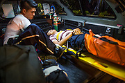 """30 NOVEMBER 2012 - BANGKOK, THAILAND: A man injured in a motorcycle accident is taken out of an ambulance by volunteer medics with the Ruamkatanyu Foundation during a Friday night shift. The Ruamkatanyu Foundation was started more than 60 years ago as a charitable organisation that collected the dead and transported them to the nearest facility. Crews sometimes found that the person they had been called to collect wasn't dead, and they were called upon to provide emergency medical care. That's how the foundation medical and rescue service was started. The foundation has 7,000 volunteers nationwide and along with the larger Poh Teck Tung Foundation, is one of the two largest rescue services in the country. The volunteer crews were once dubbed Bangkok's """"Body Snatchers"""" but they do much more than that now.    PHOTO BY JACK KURTZ"""