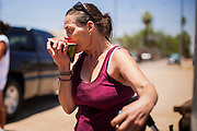 """20 JUNE 2012, PHOENIX, AZ:  A homeless woman eats watermelon provided by """"I Will Listen"""" in Phoenix, AZ, Wednesday. June 20 is the first day of summer in the northern hemisphere. The high temperature in Phoenix Wednesday soared to over 110 (F), well above the normal of 105. The hot weather is especially stressful on the homeless, who don't have the opportunity to get into air conditioning or access to cold water. """"I Will Listen,"""" an outreach organization that assists the homeless and community of street people in Phoenix, AZ, provides free food and cold drinks to the homeless in central Phoenix. They ran out of drinks and food in about one hour during Wednesday's outreach.       PHOTO BY JACK KURTZ"""