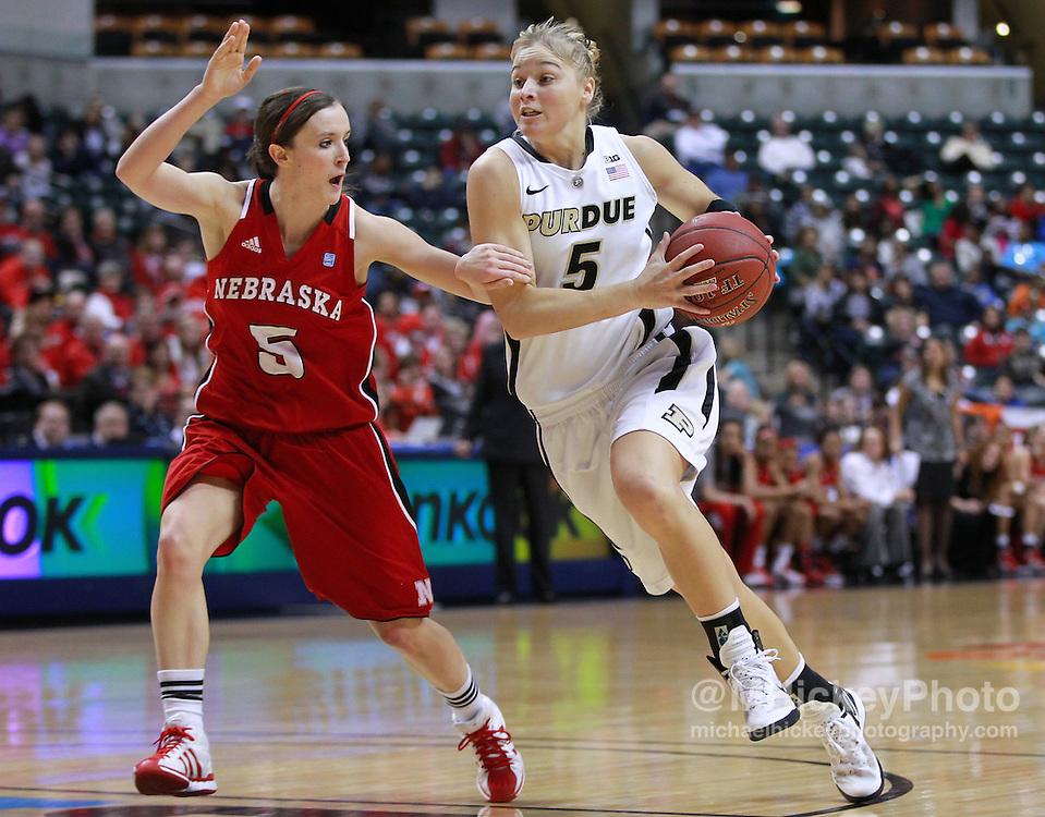 March 04, 2012; Indianapolis, IN, USA; Purdue Boilermakers guard Brittany Rayburn (5) dribbles around Nebraska Cornhuskers guard Kaitlyn Burke (5) during the finals of the 2012 Big Ten Tournament at Bankers Life Fieldhouse. Purdue defeated Nebraska 74-70 in 2OT. Mandatory credit: Michael Hickey-US PRESSWIRE