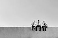 Black and white photo of thoughtful businessmen sitting and relaxing on rooftop