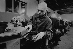 Russian juvenile prisoner cleans his tadle after his eat at the colony for prisoner's children in Siberian town Leninsk-Kuznetsky, Russia, 26 January 2000.
