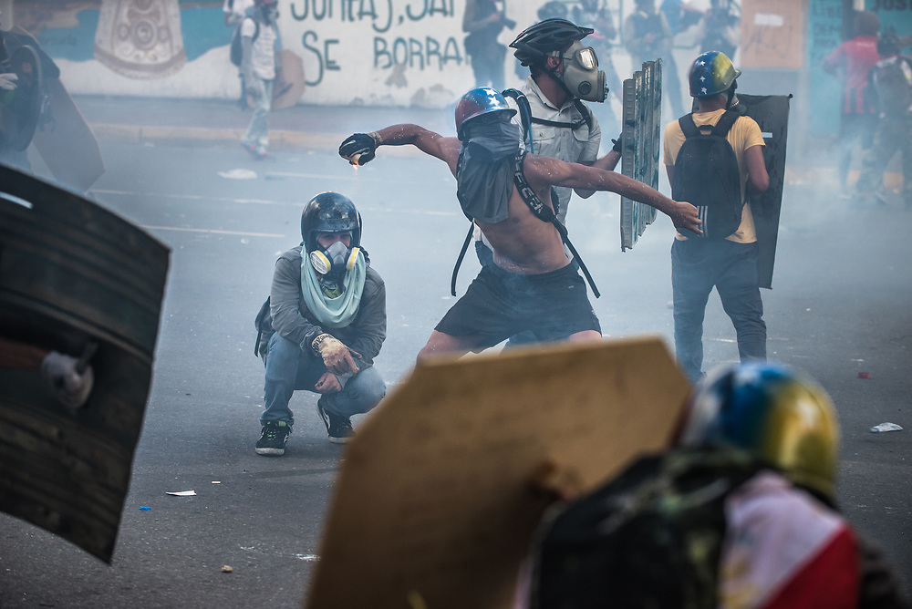 CARACAS, VENEZUELA - MAY 20, 2017:  Anti-government protesters hurl stones and molotov cocktails during clashes with members of the National Police, who responded by heavily tear gassing and firing rubber bullets and buckshot at them. The streets of Caracas and other cities across Venezuela have been filled with tens of thousands of demonstrators for nearly 100 days of massive protests, held since April 1st. Protesters are enraged at the government for becoming an increasingly repressive, authoritarian regime that has delayed elections, used armed government loyalist to threaten dissidents, called for the Constitution to be re-written to favor them, jailed and tortured protesters and members of the political opposition, and whose corruption and failed economic policy has caused the current economic crisis that has led to widespread food and medicine shortages across the country.  Independent local media report nearly 100 people have been killed during protests and protest-related riots and looting.  The government currently only officially reports 75 deaths.  Over 2,000 people have been injured, and over 3,000 protesters have been detained by authorities.  PHOTO: Meridith Kohut
