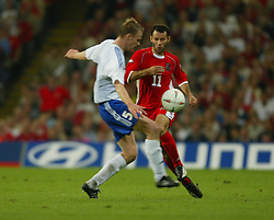 CARDIFF, WALES - Wednesday, September 10, 2003: Wales' Ryan Giggs takes on Finland's Hannu Tihinen during the Euro 2004 qualifying match at the Millennium Stadium. (Pic by David Rawcliffe/Propaganda)