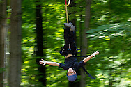 Town of Wallkill, New York - Jake Raymond flies down a zip line while during a Ninja Warrior Day Camp trip to Ring Homestead Camp on July 8, 2014.
