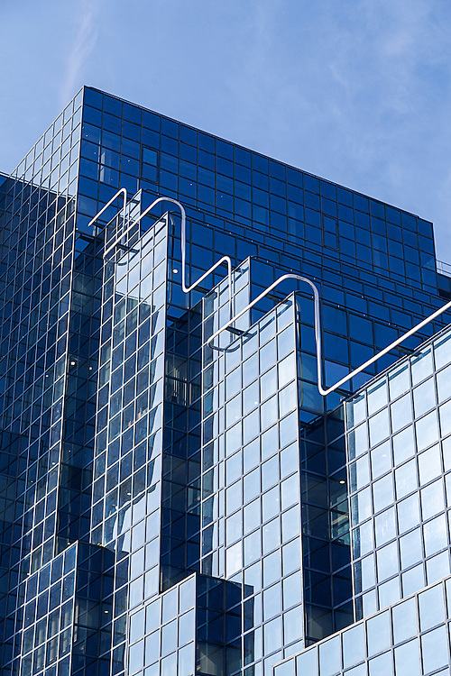 Vivid blue office building with plate glass walls and gleaming steel structure.