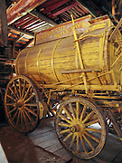 "An antique yellow-painted wooden water tank wagon of the ""Virginia City Water Works"" is preserved at Nevada City, Montana, USA. Nevada City was a booming placer gold mining camp from 1863-1876, but quickly declined into a virtual ghost town. This fascinating town inspires you to imagination what life must have been like in early Montana when gold was discovered at nearby Alder Gulch. More than 90 buildings from across Montana have been gathered for preservation at Nevada City, mostly owned by the people of the State of Montana, and managed by the Montana Heritage Commission. In 2001, the excellent PBS television series ""Frontier House"" used one of the buildings and its furnishings to train families in re-creating pioneer life. A miner's court trial and hanging of George Ives in the main street of Nevada City was the catalyst for forming the Vigilantes, a group of citizens famous for taking justice into their own hands in 1863-1864. Directions: go 27 miles southeast of Twin Bridges, Montana on Highway 287."