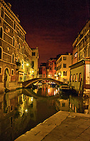 Beautiful canal scene with bridge at night in Venice, Italy with golds, reds and yellows and reflections on the canal.