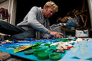 Local Ventura artist, Chris Charney, assembles one of his 'trash art' pieces outside his home in Ventura, Calif., on Thursday, June 9, 2011.  Charney will periodically scan the beaches near his home, bringing back the bits of detritus he finds to use in these unique sculpture paintings.  This one is set to hang in the Ventura Museum. (Photo by Aaron Schmidt © 2011)